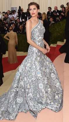 ALLISON WILLIAMS in a custom one-shoulder Peter Pilotto gown with a full skirt and side cutout, adorned with flowers and 3D appliqués, plus a La Ligne x Edie Parker clutch she helped design. Her earrings are Soraya Silchenstedt x La Ligne, in her hair, Erickson Beamon and Stephen Russell jewels. Met Gala 2016