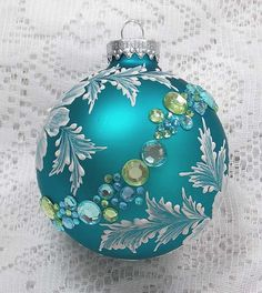 Margot Clark created this soft turquoise ornament with White 3D texture painted MUD floral design and added multi-colored rhinestone trim. Each ornament created is a one-of-a-kind. The texture medium and paint brush used to paint the ornaments were both created to my specifications. My signature M is located on the bottom of the ornament. Gift boxed. Measures 3 x 3 Ornament weight is 2 ounces.