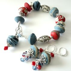 Love this color combination! Beautiful denim blue with hints of darker blue and sand tones, a few silver dots, just perfect with the brick red companion beads. Ive used open scrollwork silver beads and silver discs to compliment the lampwork and just a hint of Swarovski crystals on the bracelet dangle (the dangle helps keep the weight at the bottom of your bracelet and keeps it from turning around on your wrist. This bracelet will fit a wrist from 6 to 6 3/4 depending on how you like you...