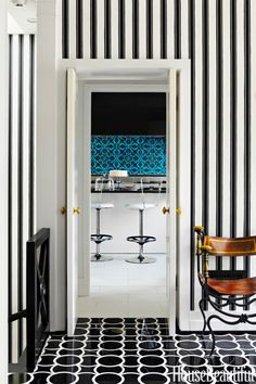 """Graphic patterns extend from the foyer in a Washington, D.C. town house through to the kitchen. """"We both like snappy architectural solutions — like the patterned floor and striped wallpaper — that give black-tie panache to small spaces,"""" designer Jeff Lincoln says of the house he designed with Hillary Thomas. The black and white of Montgomery 1 marble floor tiles by Ann Sacks and Block Print Stripe wallpaper by Farrow & Ball is reminiscent of Dorothy Draper.   - HouseBeautiful.com"""