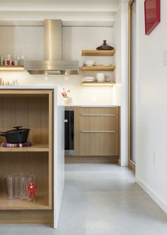 Kitchen, Concrete Floor, Wall Oven, Range Hood, Laminate Counter, Wood Cabinet, Porcelain Tile Backsplashe, and Accent Lighting The kitchen features white quartz counters, a mounted induction cooktop, and a full-height backsplash with white penny-round tiles.       Photo 136 of 2157 in Best Kitchen Photos