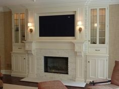 Fireplace surround and bookcases - What a nice way to incorporate a TV with out it looking like a TV above the fireplace.