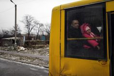 A man and a child look through a bus window before leaving as people flee the conflict in Debaltseve, eastern Ukraine, February 6, 2015. REUTERS/Gleb Garanich