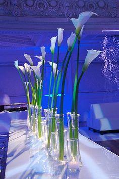 Group multiple arrangements of long-stemmed calla lilies to create a modern centerpiece
