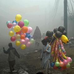 Pakistani balloon vendors cross a street in heavy fog in Lahore on December 24, 2016. AFP Photo by Arif Ali