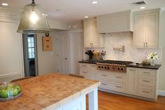 Chevron, marble backsplash, creamy-green cabients, black coutners. Venegas and Company