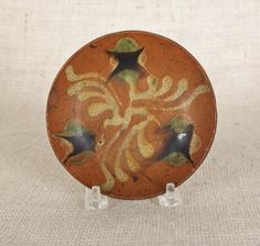 Sold For  $ 5,500                                                          Pennsylvania redware tart plate, 19th c., with yellow, green, and manganese slip decoration of wavy lines and stars, 4 5/8'' dia.                            Condition report           1/4'' x 7/8'' rim chip.  Another small rim flake.  Otherwise very good condition. |Pinned from PinTo for iPad|