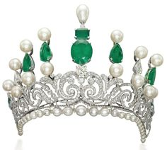 AN IMPRESSIVE EMERALD, NATURAL PEARL, CULTURED PEARL, AND DIAMOND TIARA. The Belle Epoque diamond-set scroll tapering bandeau on a later added base of graduated cultured and natural pearls with diamond rondelle spacers, to the later added graduated bar surmount set with cultured and natural pearls, emeralds and diamonds, inner diameter 14.5 cm.