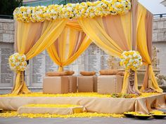 Love the draping and floral work on this ochre yellow, dull brown and white wedding mandap #floral mandap