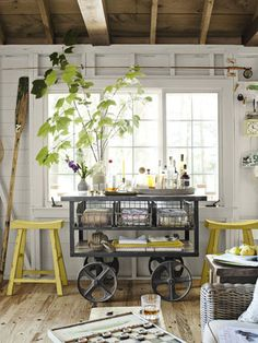 A wheeled iron cart doubles as a portable bar and stylish storage. Both that piece and the reclaimed-elm stools are by Arhaus Furniture.
