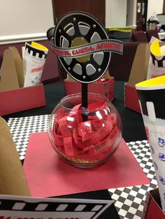 Movie theatre themed decor used for our big annual training. These are the centerpieces in each table - a fish bowl with popcorn kernels, tickets, and a movie reel. Also used scrapbook paper as a background to set the centerpiece on.