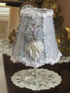 You are viewing an old vintage lampshade that I have redesigned using light periwinkle blue lace. In addition I have added tiny French silk buds