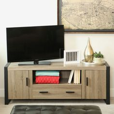 What's old is new again with this urban reclaimed 60 inch TV stand. Features large storage drawer, private cabinets and spacious shelving for media. Will accommodate most flat-panel TVs up to 65 in. Constructed of powder-coated steel and wood.