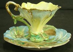 NIPPON DEMI TASSE CUP AND SAUCER IN THE SHAPE OF A MORNING GLORY BLOSSOM ON A MATCHING SAUCER WITH SAME FLOWERS AND LEAVES.
