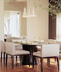 Sala de jantar Mesa ovalada para proporcionar uma boa circulação com tampo de vidro e pé de imbuia com ranhuras. Cadeiras de assento largo estofadas de seda clara contrastante.