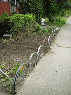 Old metal bike rims make a cute fence for your garden.