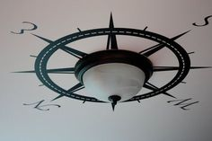 Neat idea to place a compass rose wall decal on the ceiling around a ceiling light. Adventure is out there! could use removable vinyl decals for rental properties or dorm rooms or classrooms - ways to decorate a room on a budget for kids playrooms - how to decorate low ceilings without adding bulk - space saving apartment ideas