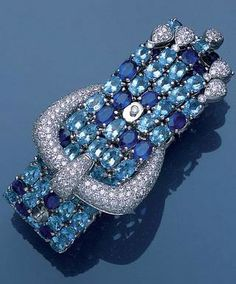 An aquamarine, sapphire and diamond jarretière bracelet, The articulated strap of oval mixed-cut sapphires and aquamarines, to a pavé-set diamond buckle clasp and pavé-set diamond tassel, length 22.5cm.