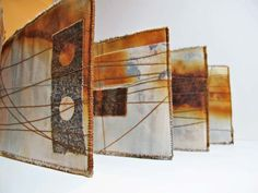 Jennifer Coyne Qudeen - beeswax painted over rusted cloth stitched lengthwise with a only a few vertical lines. The marks left on the newsprint after ironing to remove the excess wax were fascinating - and were used as well.