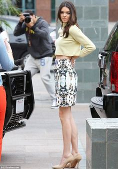 Endless legs: Kendall Jenner displayed her enviably slim figure in a lemon coloured sweater, patterned mini skirt and nude heels as she arri...