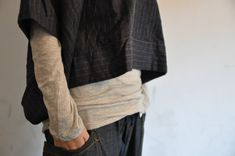 looks like a quality textile in a rectangle with arm holes. juxtaposed with the soft gray knit underlayer