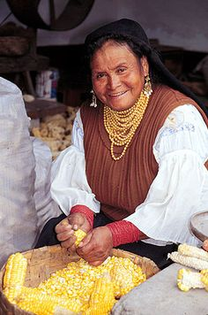Otavalo, Ecuador.An old woman husking corn as part of her daily chores. She is the wife of a master weaver, and we were in their home for a short time talking to them.