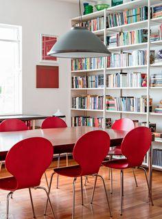 """Como o projeto anterior não incluiu forro de gesso, Gustavo incrementou a iluminação instalando lâmpadas fluorescentes no topo das estantes. """"Isso faz uma bonita contraluz nos objetos"""", explica. Ele também recorreu a abajures e pendentes. Este, acima da mesa da Montenapoleone, é da Reka. Cadeiras da Tok Stok."""