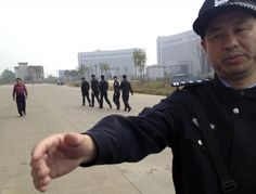 A Chinese police officer reaches out towards a journalist outside the courthouse where a trial of Chinese activists is underway in Xinyu city in eastern China's Jiangxi province on Monday, Oct. 28, 2013. Three Chinese activists from a group that urges fellow citizens to embrace their constitutional rights stood trial Monday in the Xinyu district court in a closely watched case that underscores the Communist Party's intolerance of organized political challenge - no matter how small. (AP…