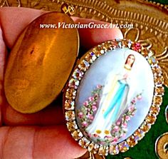 $89 Vintage Rhinestone Cameo Locket Our Lady of Lourdes (Image1)Vintage porcelain cameo pendant locket featuring the Blessed Mother Virgin Mary as Our Lady of Lourdes of the Rosary standing in pink roses, hands folded in prayer. Golden AB rhinestones and 1 pink rhinestone accent. The vintage locket can hold 2 photo's and/or your prayer petition request to Our Lady.