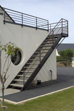 Photo montrant l'escalier extérieur qui amène au premier niveau et la terrasse de la maison