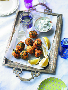 These spicy lentil fritters are served with lemon wedges and raita.