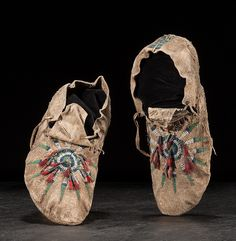 Crow Soft-Soled Moccasins thread sewn with beaded sun burst design on vamp; tin cones and dyed horse hair embellishments; beadwork in pea green, opaque white and translucent indigo; length 10.5 in. fourth quarter 19th century. Cowan's Auctions. September 2017.