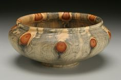 Norfolk Island Pine Bowl: Turned on the end grain from a solid piece of Norfolk Island Pine, this piece is circled by knots from the original tree's branches. 7 w x 3 1/2 h.