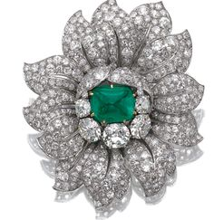 EMERALD AND DIAMOND CLIP, VAN CLEEF & ARPELS Designed as a stylised flower head, set at the centre with a sugar loaf cabochon emerald within surrounds of cushion-shaped, single-, circular- and brilliant-cut diamonds, mounted in platinum.  Sotheby's.