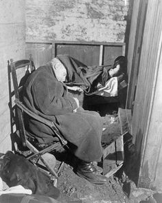An elderly man sleeps on an old wooden chair, whilst a lady covered with a blanket lies on a bed of boxes, under the railway arches somewhere in South East London, probably in November 1940.  It is not possible to identify which of the many railway arches used as air raid shelters during the Second World War is featured in this sequence of photographs, although it is probable that it is at Dockley Road in Bermondsey. Stainer St. Arch and Druid St. Arch in Bermondsey were both used as…