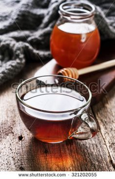 cup of hot tea in  glass cup,  jar of honey, honey dipper on the old wooden background (black style)