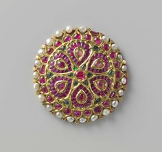 Hair ornament, gold in the form of a rosette. Inlaid with red and green stones and diamond chips. Made in Surat, ca. 1750