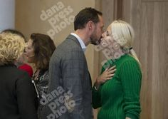 Prince Haakon and Princess Mette-Marit.give each other a kiss while hosting a conference.