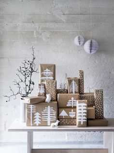 "Christmas presents are wrapped with brown kraft paper. Decorations are made from white paper cut into tree shapes. Glue the paper trees onto the package. White paint pens create the ""snowfall"" design."