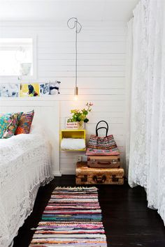 Dark floor. white walls. bright rug.