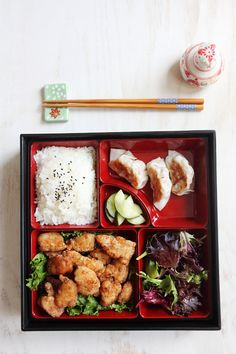 Japanese Fried Chicken Bento with steamed rice and sesame seeds, pickled cucumbers, salad and Gyoza.