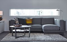 A living room with a two-seat sofa with chaise longue in a dark grey cover and a black-brown coffee table