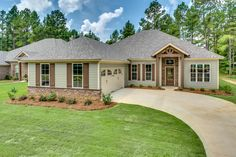 Beautiful house with light green siding combined with a stone accent exterior along with dark brown wood paneled shutters, a two car garage, and light brown trim.