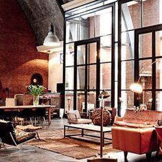 Er staan een heleboel meubels in deze kamer. 3 lampen en veel grote, open ramen.