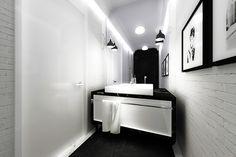 Aranżacja wnętrz czarno-białej łazienki w klasycznym stylu - Tissu. Elegancka łazienka z cegłą i czarnymi meblami jest powiększona dzięki ścianie z lustrem. Czarna podłoga dzięki białym paskom po bokach wygląda jak elegancki dywan podkreślający podłużny kształt pomieszczenia. http://www.tissu.com.pl/zdjecia/390,z-nuta-romantyzmu-apartament-piastow-80m2