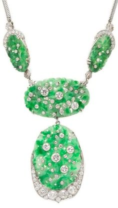 An Art Deco Platinum, White Gold, Jade and Diamond Convertible Necklace. The detachable central pendant/brooch composed of two pierced and carved oval jade plaques, the lower set within a partial platinum surround and both plaques studded with diamonds, with detachable white gold brooch fittings suspended from a detachable back chain composed of two pierced and carved oval jade plaques within partial platinum surrounds and studded with diamonds extending to the white gold serpentine chain.