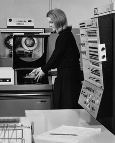 Computer operator changing a removable disk pack on a drive on an IBM System/360.