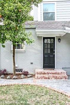 gray house with brick steps and black door | maisondepax.com... metal grate insert in crawl space vent