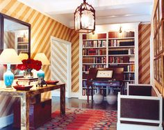 diagonal striped walls (in gold?!), mirrored Parsons console, mirror, rad rug, bookshelves, #entryway