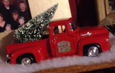 Small red truck hauling small tree